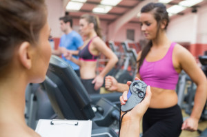 Female instructor using stopwatch in the gym